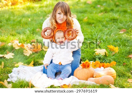 Woman with child in autumn park. Happy family. A young mother and her baby fall fun - stock photo