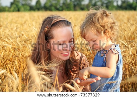 Woman with child in field of wheat - stock photo