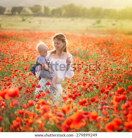 Woman with child in field with red poppies - stock photo