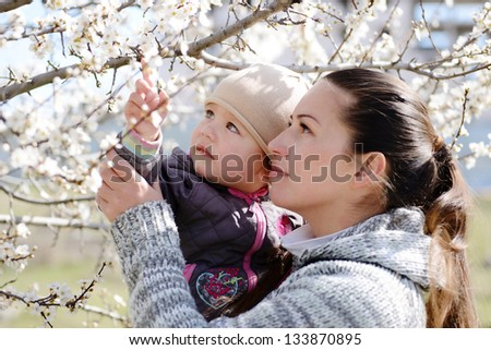 woman with child looking on  the blossom tree - stock photo