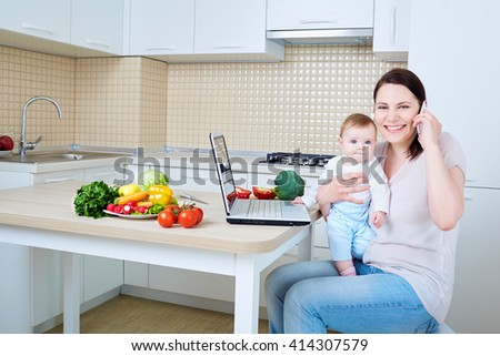 Woman with child preparing food and talking on the phone.Happy family.