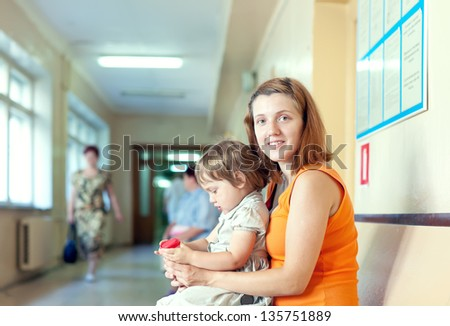 woman with child waits to attendance of doctor  at the clinic - stock photo
