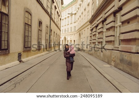 woman with child walking on lonely street