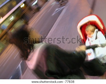 Woman with child walking on the sidewalk in a very busy city - stock photo