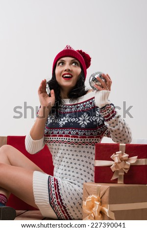 Woman with christmas gifts. Young caucasian girl looking up smiling with shopping bags and disco ball. Copy space overhead. - stock photo
