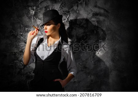 Woman with cigar on grey wall background - stock photo