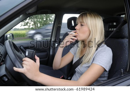 woman with cigarette and mobile phone in the car - stock photo