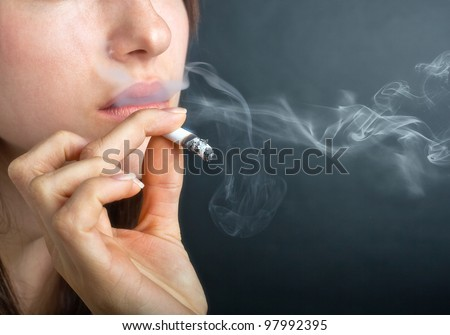 Woman with Cigarette Exhaling Smoke  on a Dark Background - stock photo