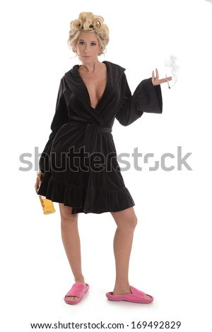 Woman with cigarette, liquor bottle, bath robe and slippers on white background  - stock photo