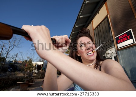 Woman with cigarette looking down a rifle barrel - stock photo