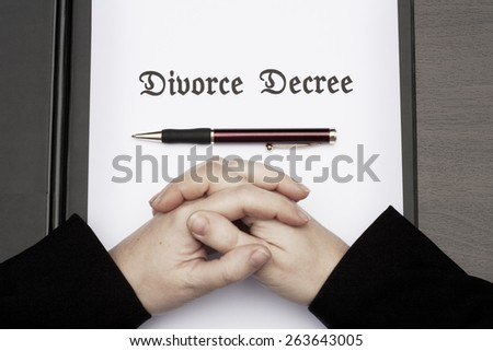 woman with clasped hands on divorce decree - stock photo