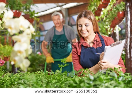 Woman with clipboard and checklist checking growth of plants in a nursery shop