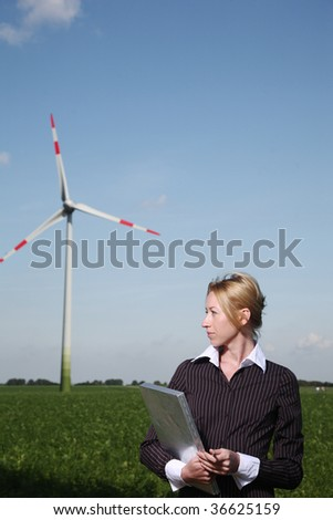 woman with clipchart stand at windturbine