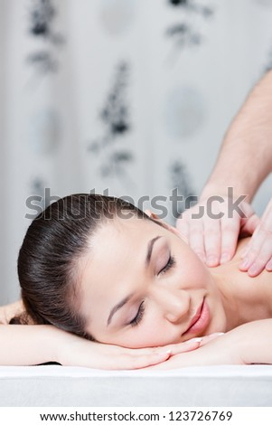 Woman with closed eyes receives body massage at spa salon