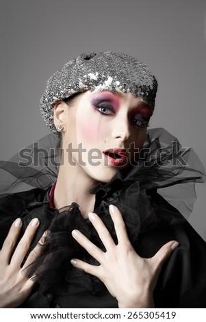 Woman with clown makeup wearing a glitter beret. - stock photo