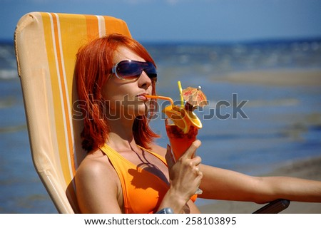 Woman with cocktail on the beach - stock photo