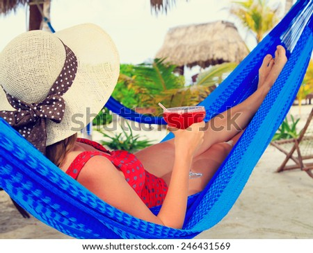 woman with cocktail relaxed in hammock on tropical beach - stock photo