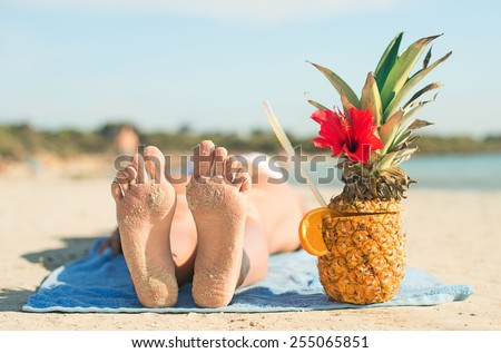 Woman with cocktail sunbathing on the beach vacation. - stock photo