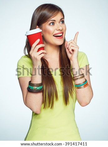 Woman with coffee cup pointing on copy space. Isolated portrait. - stock photo