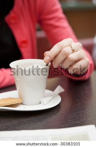 Woman with coffee reading newspaper, close-up - stock photo