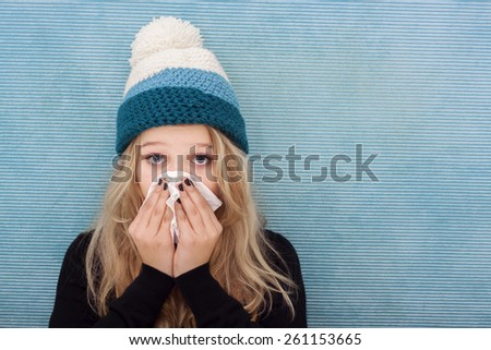 Woman with cold, blowing her nose into a tissue - stock photo