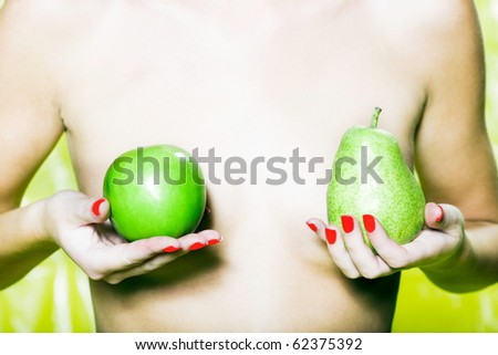 woman with colorful background holding pear and apple - stock photo