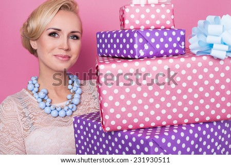 Woman with colorful jewelry holding big and small present boxes. Soft colors. Christmas, birthday, Valentine day. Studio portrait over pink background - stock photo