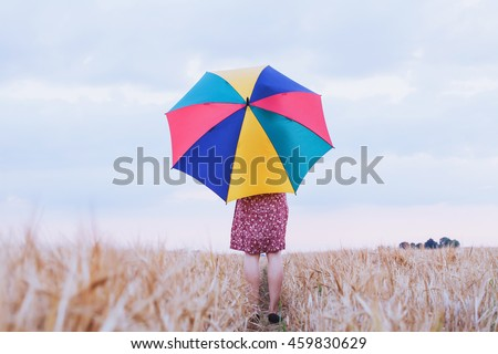 woman with colorful umbrella in the field, optimistic positive multicolored background with copyspace