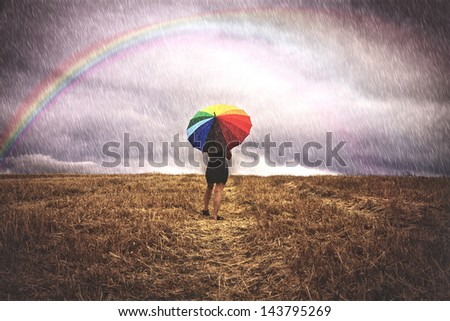 Woman with colorful umbrella in the rain for the field - stock photo