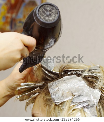 woman with coloring foil on her hair in salon - stock photo