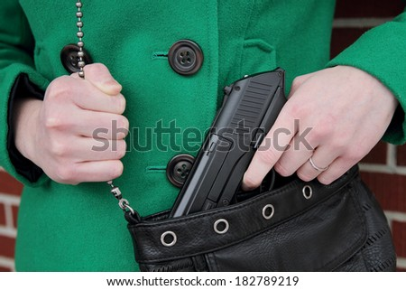 Woman with Concealed Weapon - stock photo