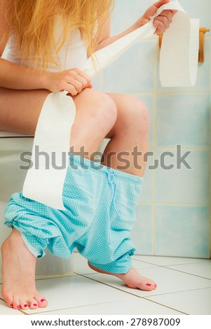 Woman with constipation or diarrhoea sitting on toilet with her blue pajamas down around her legs, holding toilet paper ready in her hands - stock photo