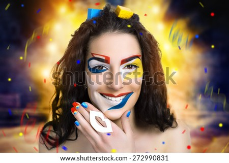 Woman with creative make up, face art design in the form of yellow, red, blue, white geometric shapes. An explosion of colorful paints, powders on the background. New idea, space for text information - stock photo