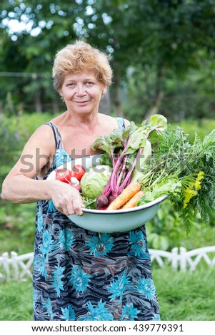 Woman with crop of fresh vegetables in the garden - stock photo