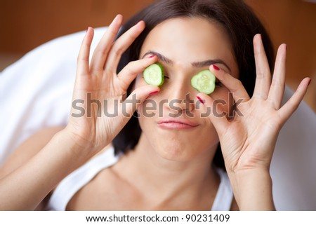 Woman with cucumbers smiles - stock photo