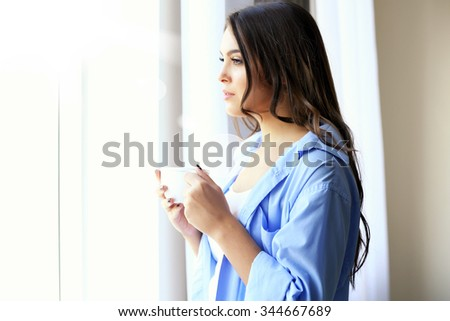 Woman with cup of coffee looking through the window in the room