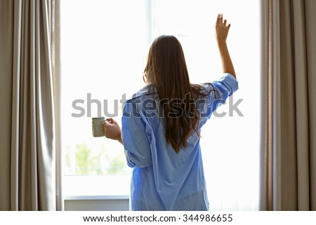 Woman with cup of coffee looking through the window in the room - stock photo