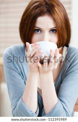 Woman with cup of tea has a rest at the coffee house - stock photo