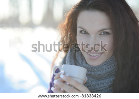 Woman with cup of tea in the winter park