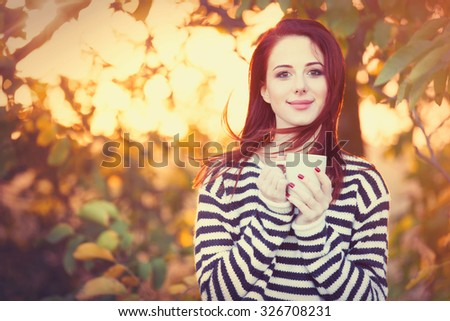 Woman with cup of tea or coffee at outdoor in autumn time - stock photo