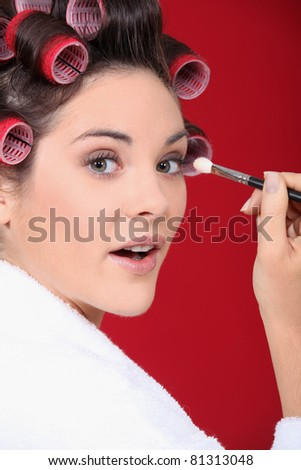 woman with curlers in her hair putting make up - stock photo
