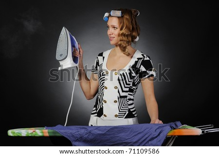 woman with curlers on her head stroking men shirt. - stock photo