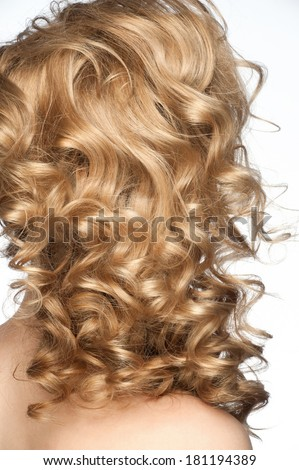Woman with curly blond hair with beautiful hairstyle. Isolated on white background, rear view