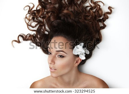 woman with curly hair and flower on it from above