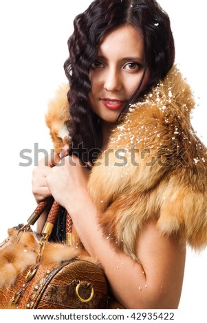 Woman with curly hair stand with leather bag with snow on her shoulders