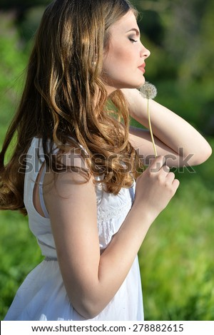 woman with dandelion in sunny day - stock photo