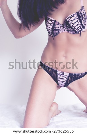 Woman with dark hair in pink and black sexy underwear with white background - stock photo