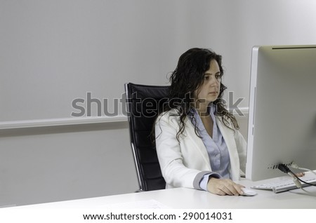 Woman with dark hair is working on computer at her office.