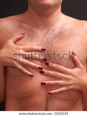 Woman with deep red fingernails embracing man's hairy torso - stock photo