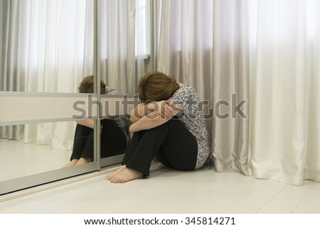 Woman with depression sitting in the corner of the room